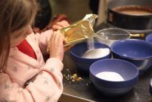 Mały kuchcik pomaga w przygotowaniu lukru na pierniki.